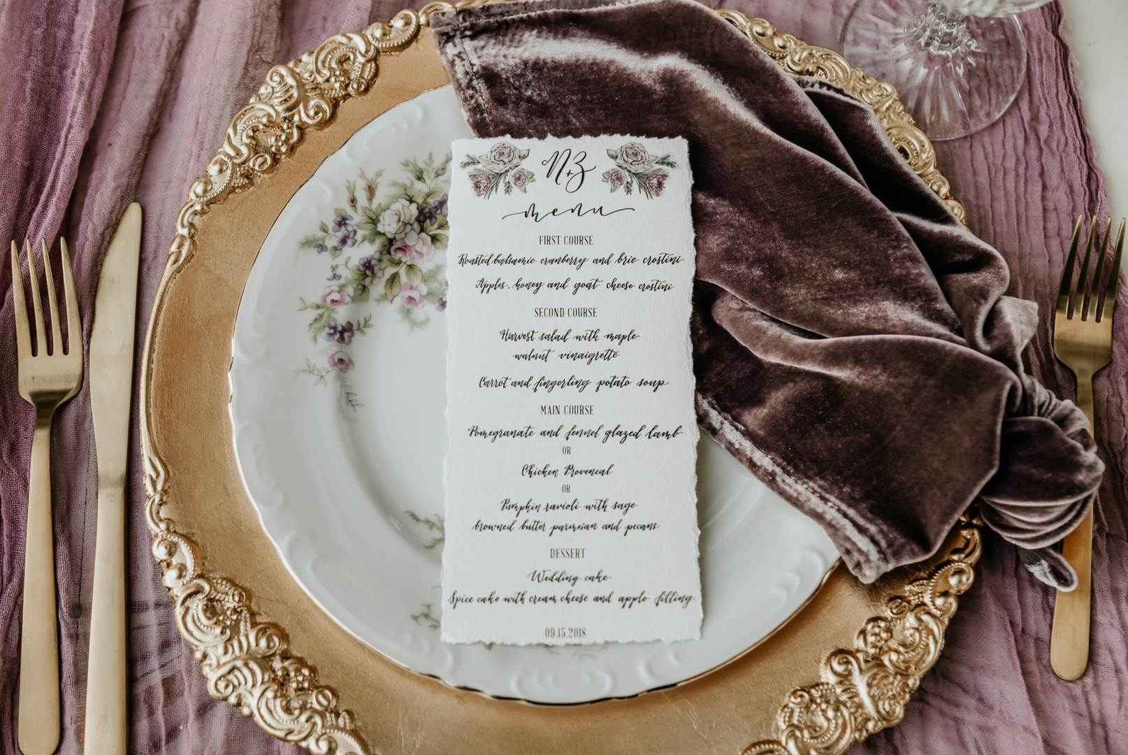 gold, white, and cream place setting with purple velvet cloth and gold utensils