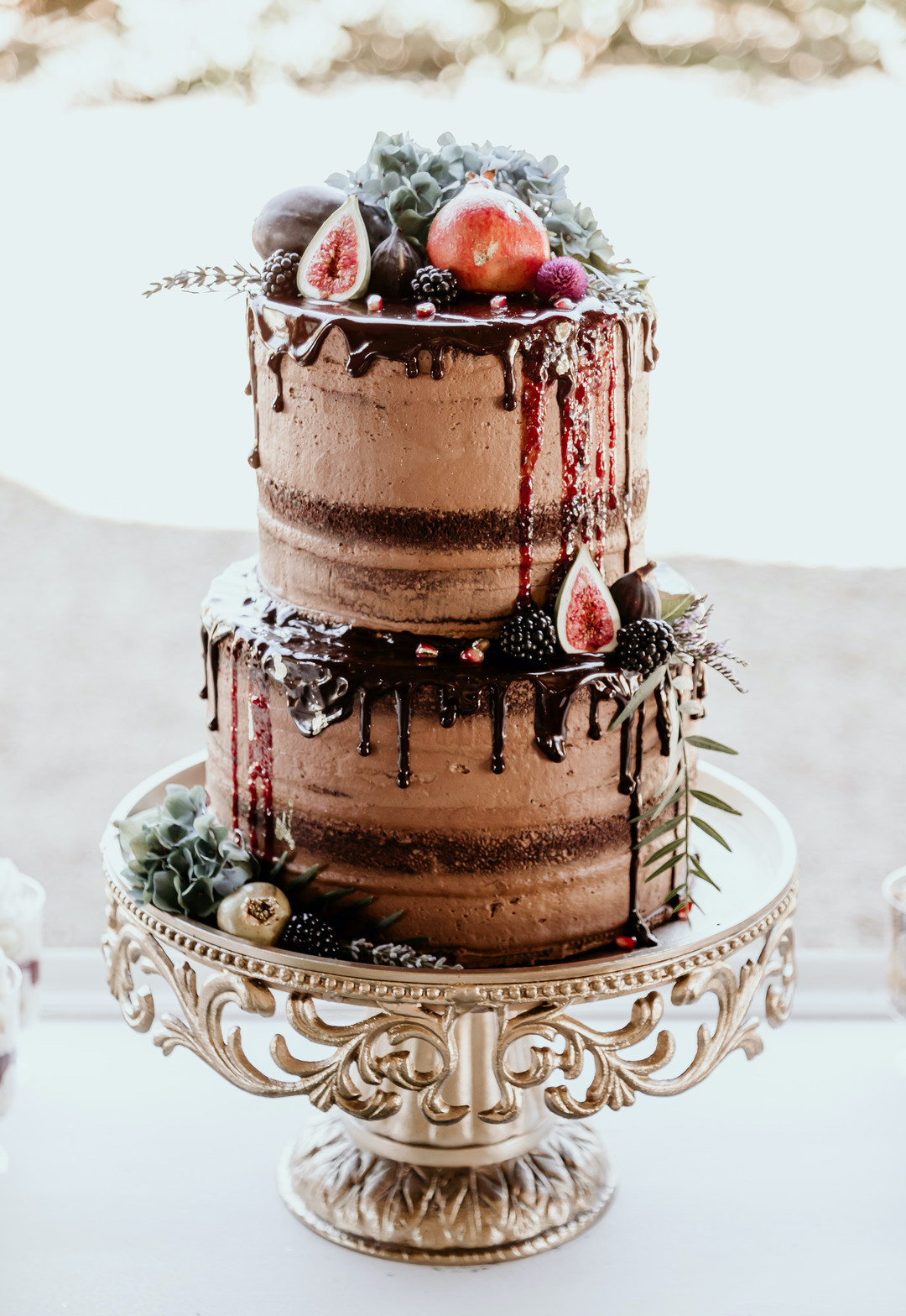 decadent chocolate cake on gold platter topped with pomegranates and berries