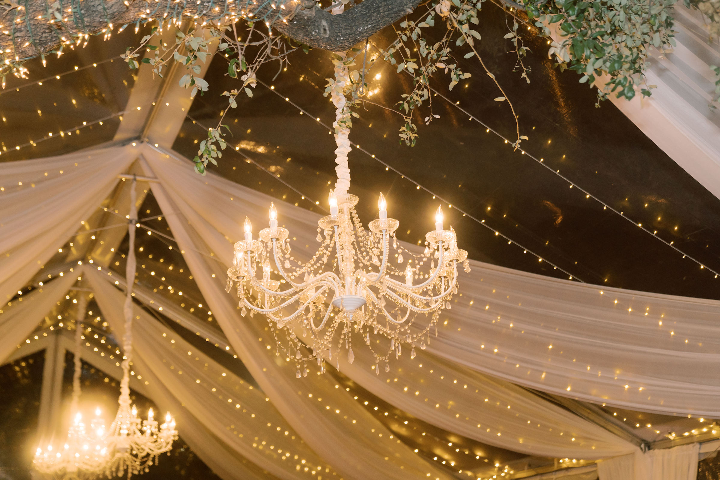 glowing chandelier hung amongst tapestries