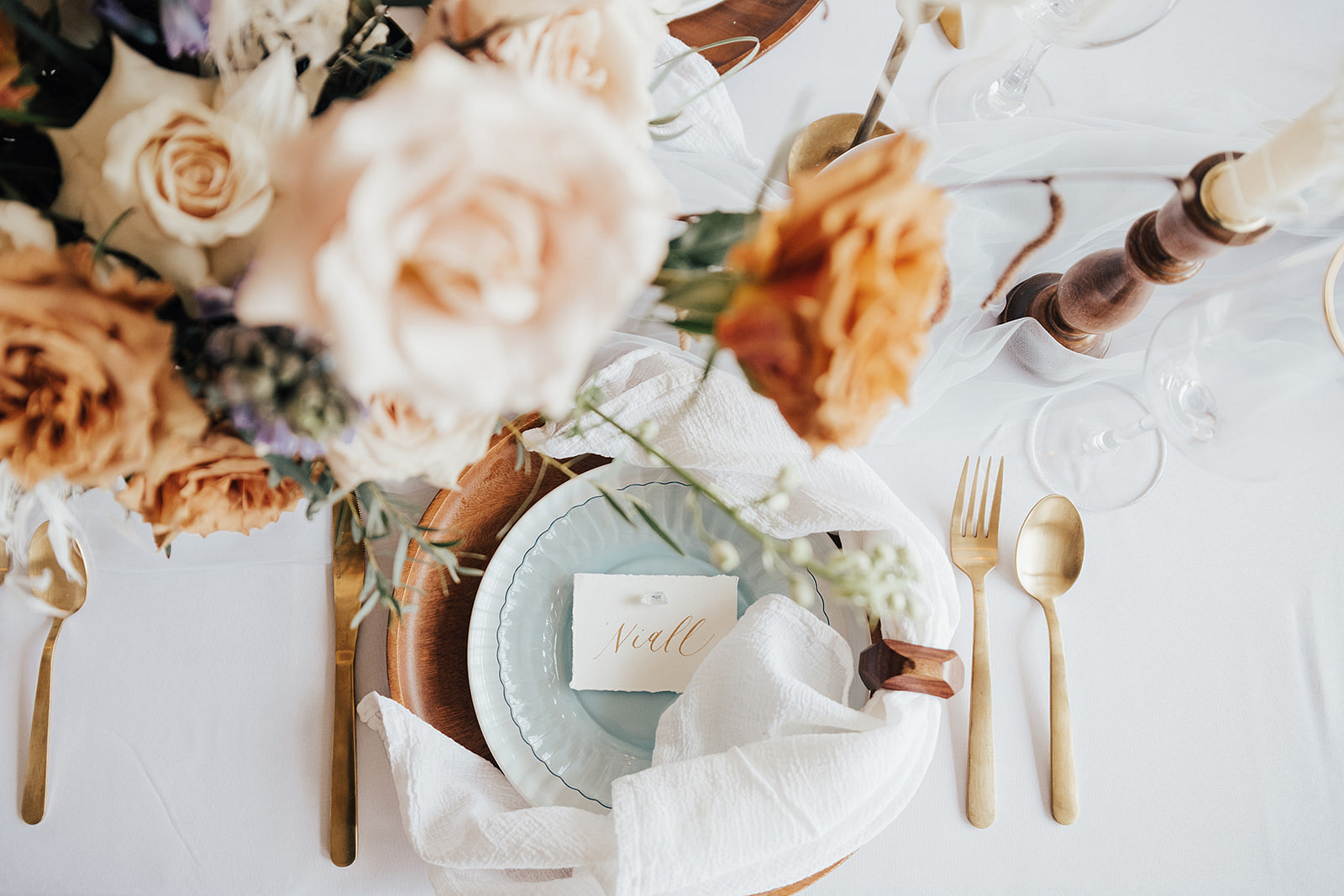 florals above a table setting with soft blue plates, gold utensils, and a place card that reads 'Niall'