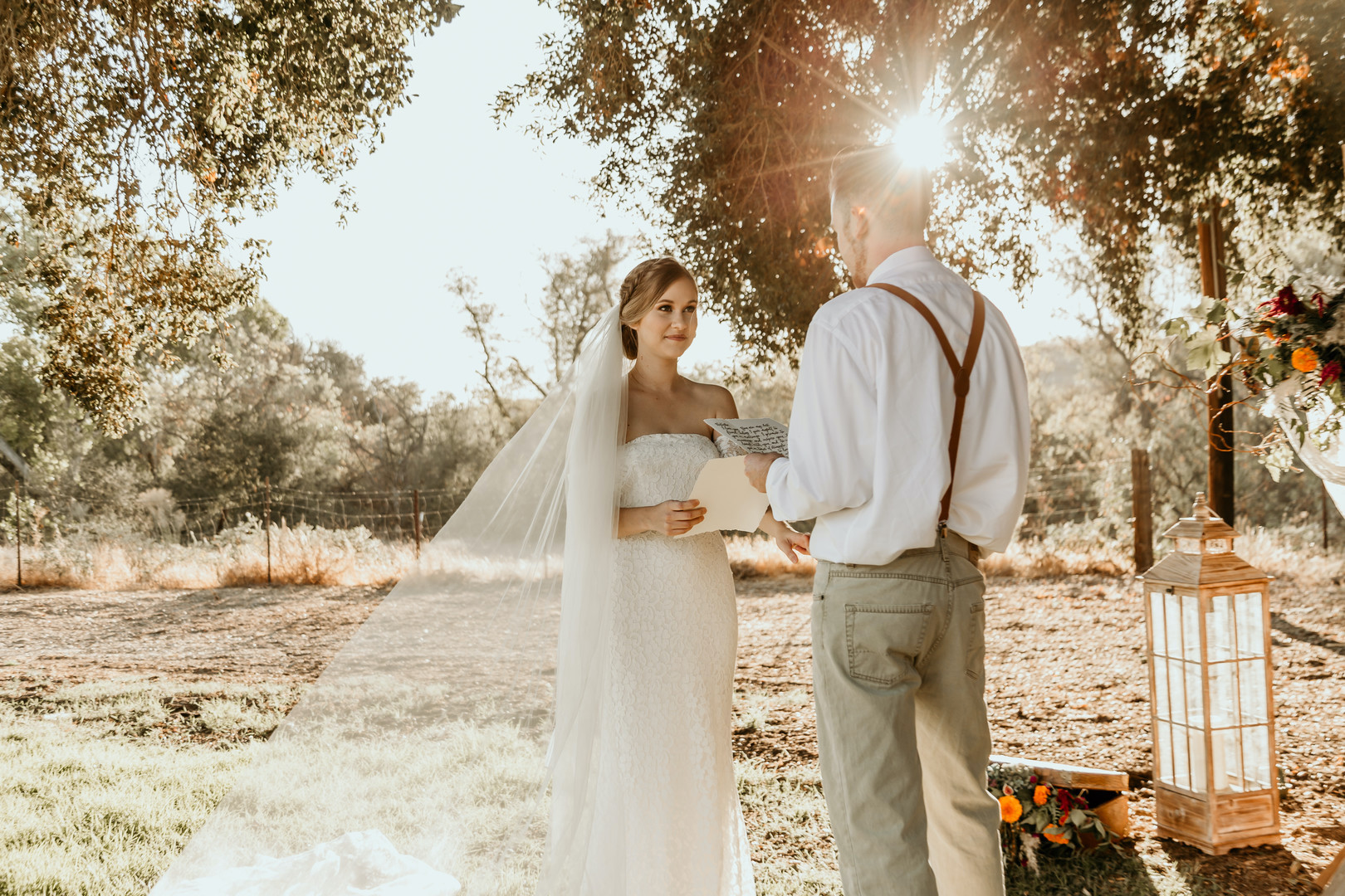 couple during outdoor wedding ceremony with rustic creekside backdrop