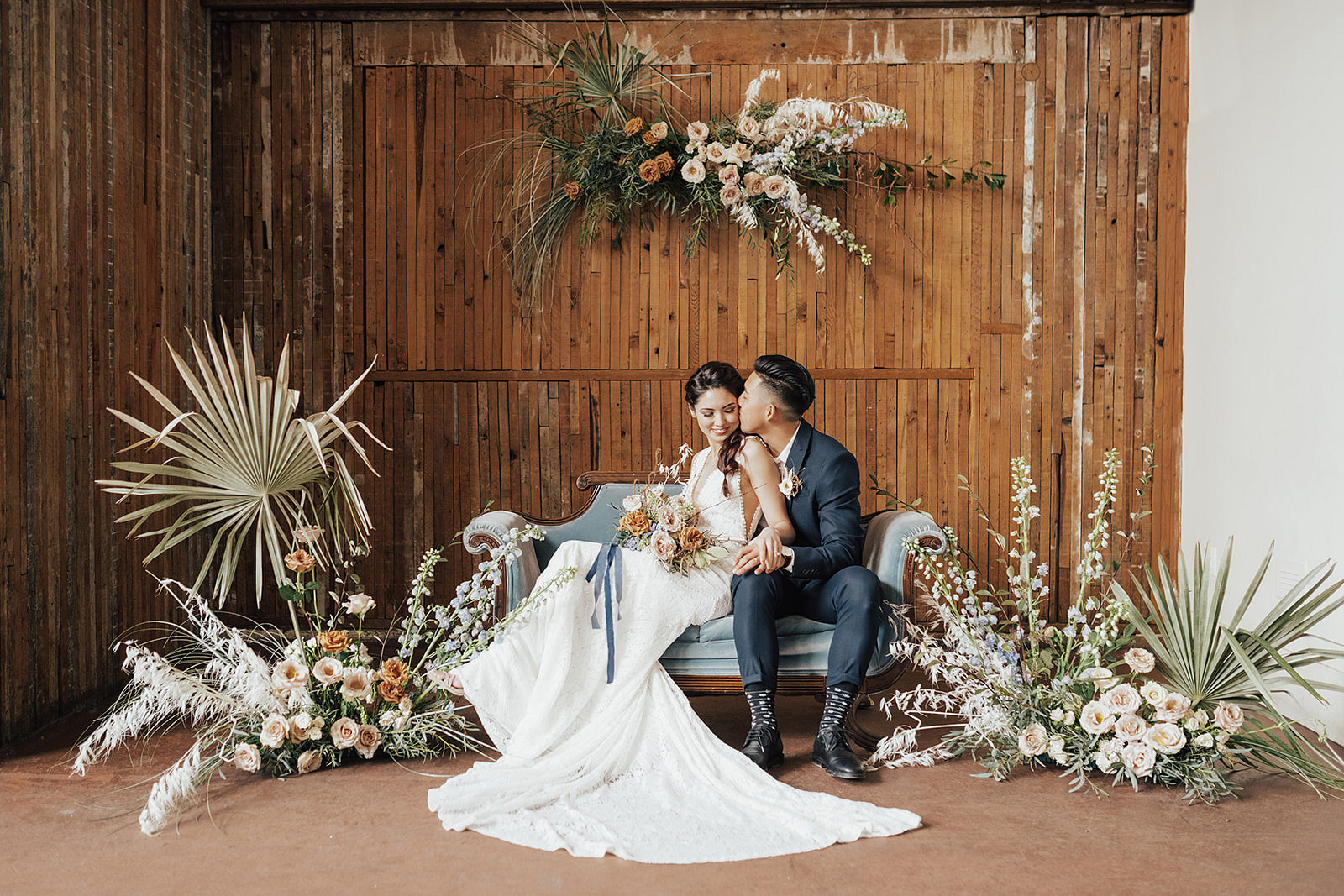 couple lounging on light blue couch with minimalist boho florals and wooden backdrop