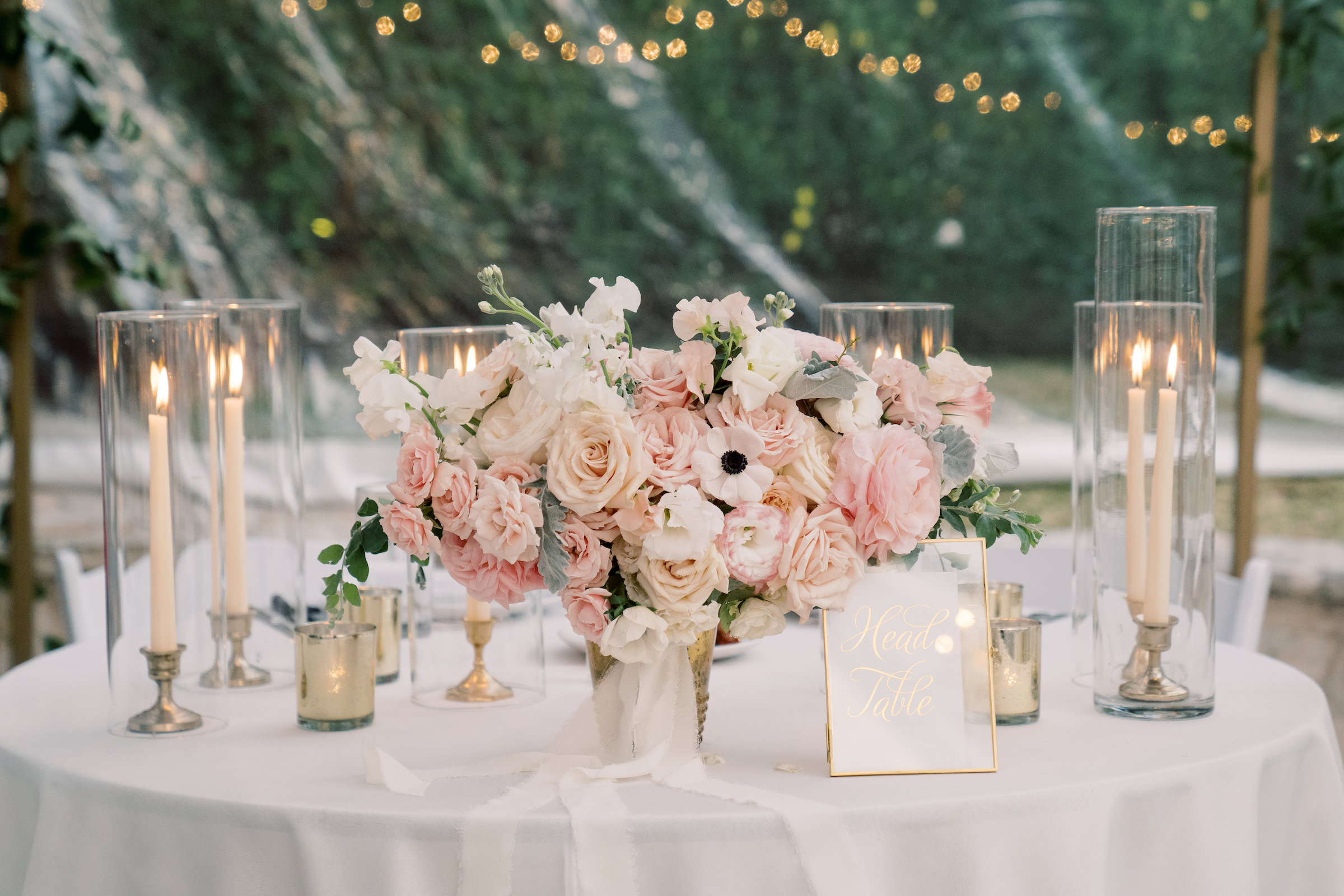 tablescape with pink and white florals among glass votives with glowing tall white candlesticks