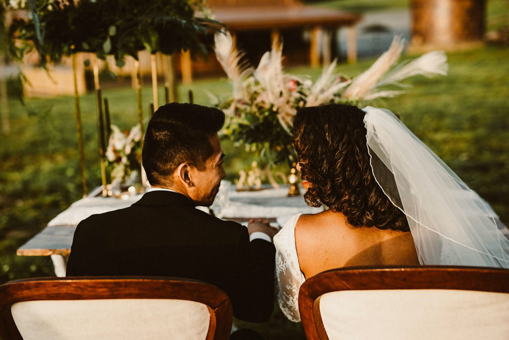 couple sitting at sweetheart table, staring at one another in marital bliss