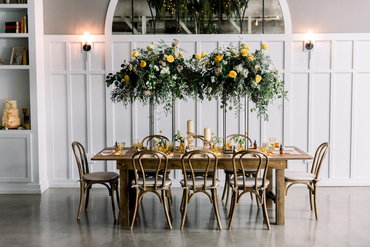 table arranged with green and yellow floral arrangment hanging above