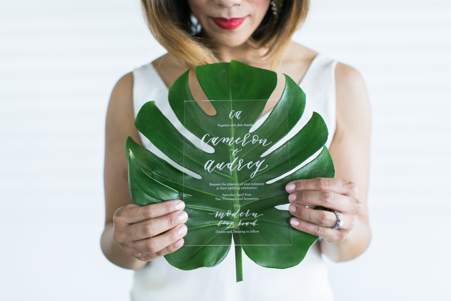 bride with bold red lip holding a banana leaf with clear invite in front
