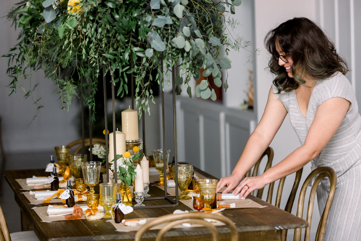 wedding planner arranging a table for a small gathering with yellow and gold themed decor