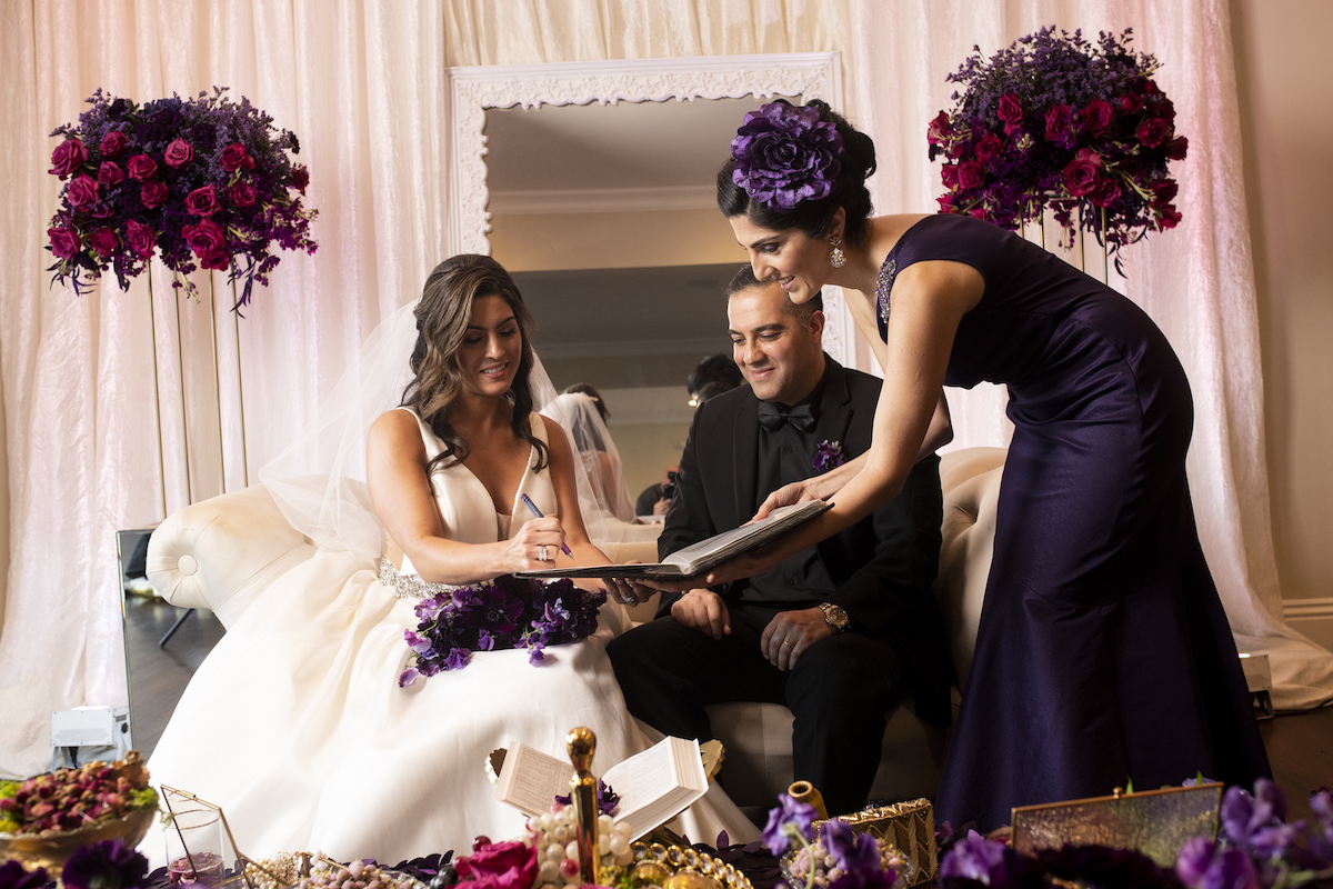 Persian couple signing documents sitting with officiant standing by