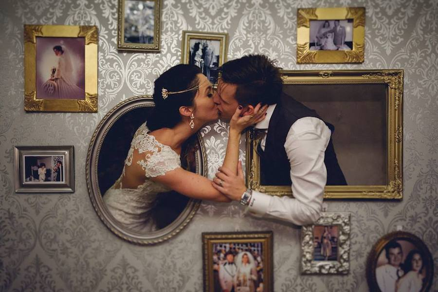 couple poking thier heads out of a photo wall kissing