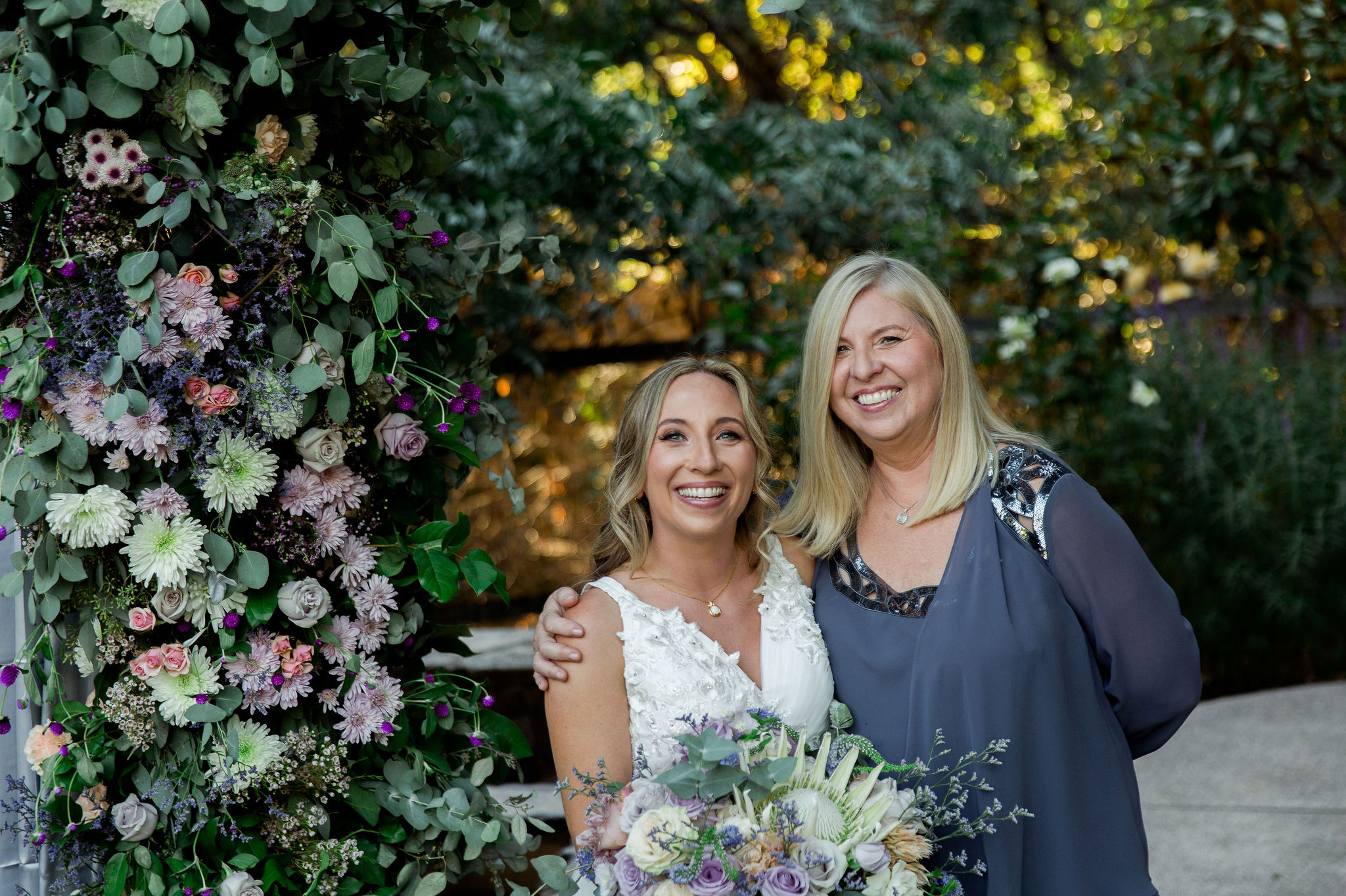 bride and her mom surrounded by florals at the wedding venue