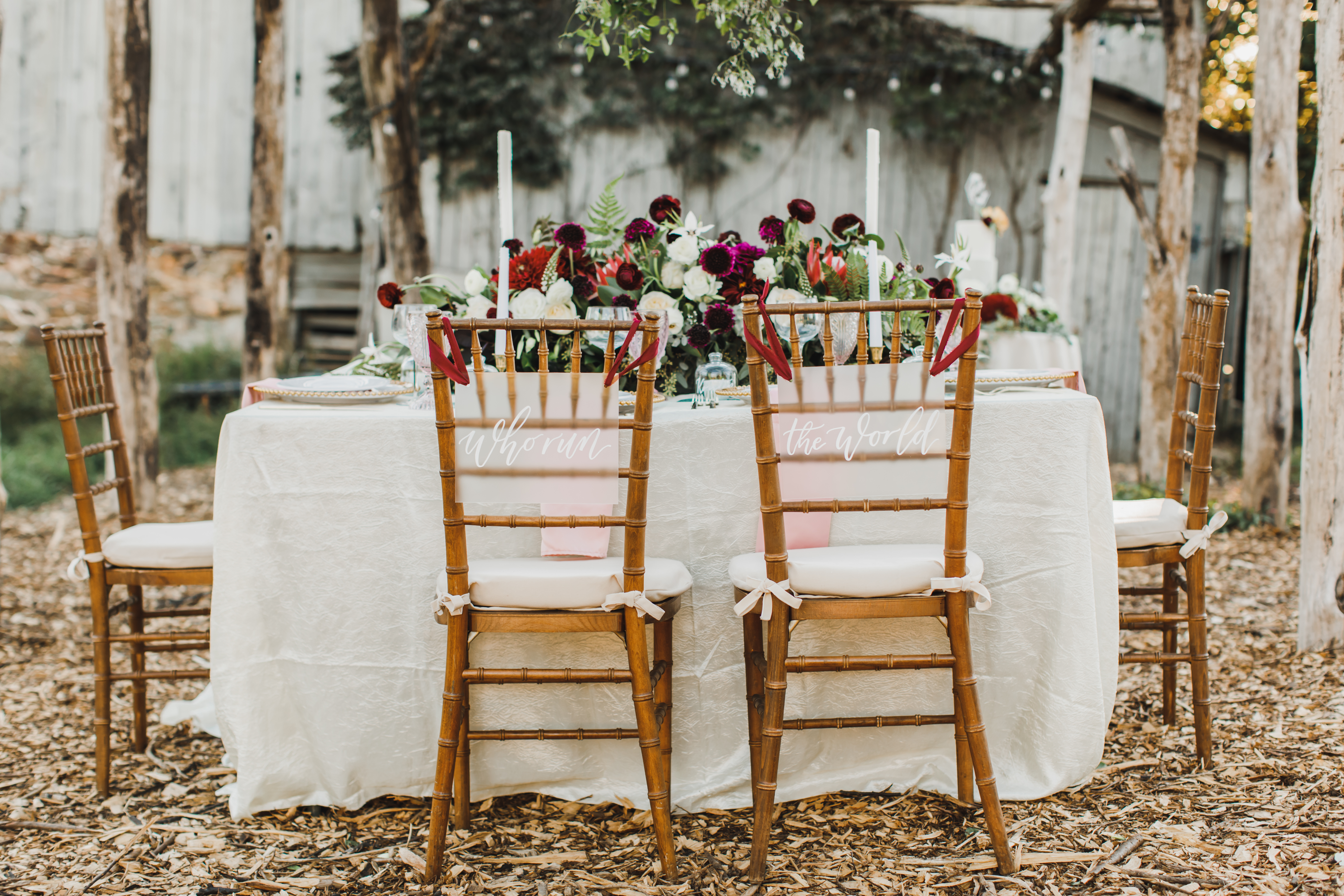 Sweetheart table chairs with signs that say 'who run the world'