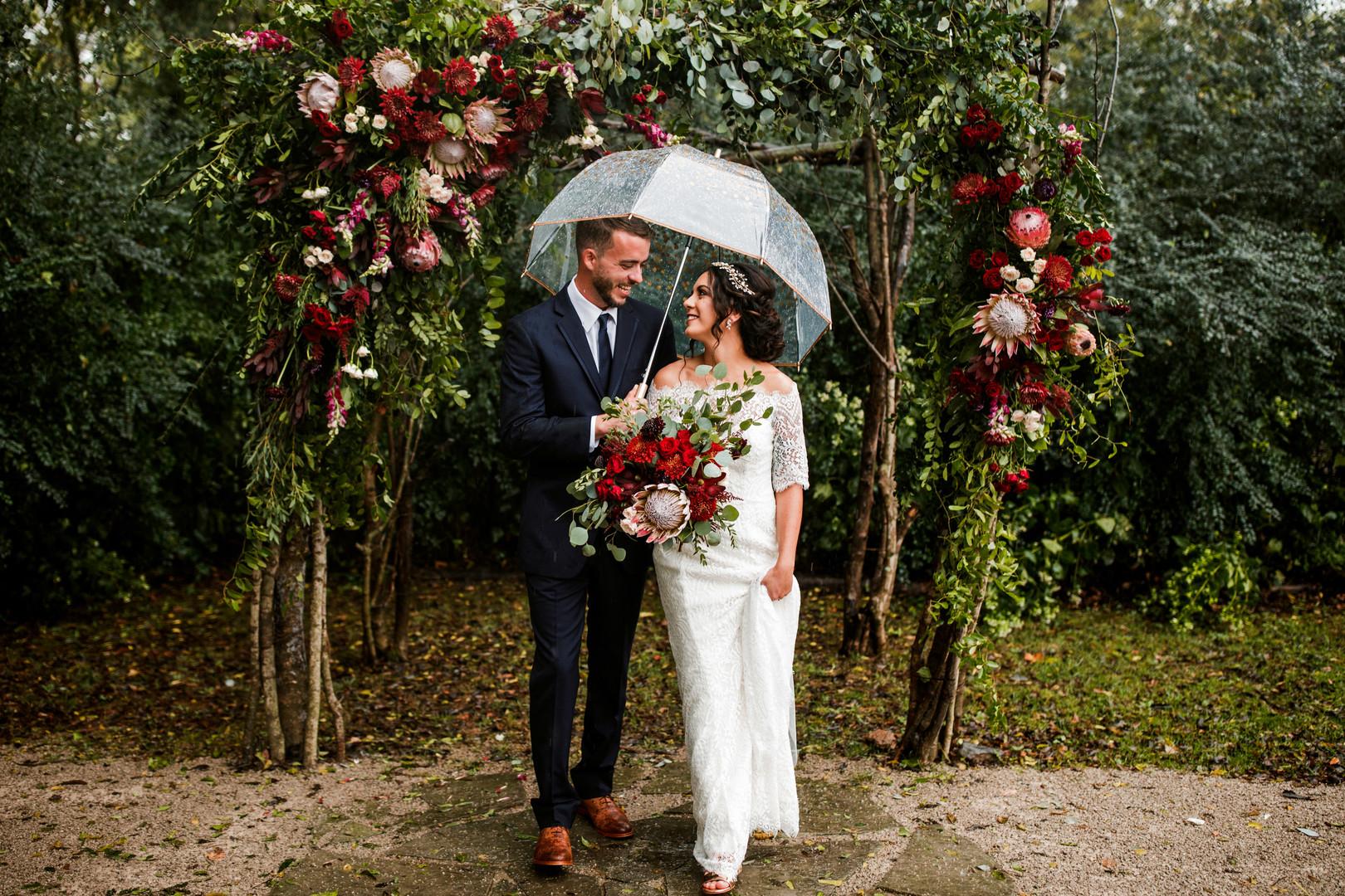 Couple under umbrella on wedding day
