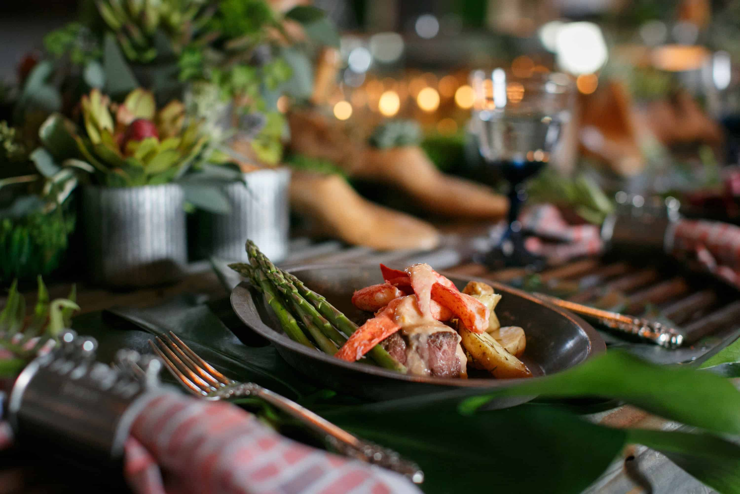 Tablescape with a dish of lobster, potatoes, and veggies