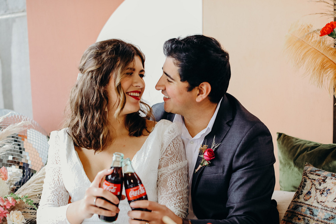 Couple looking at each other holding Coca Cola bottles