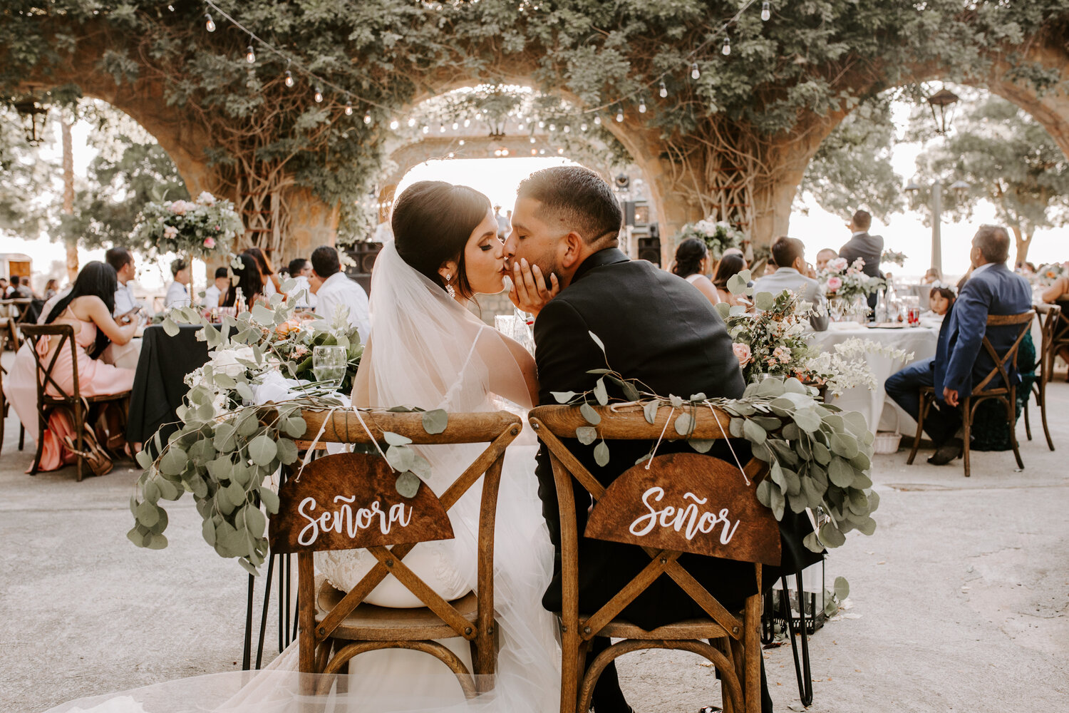 Couple kissing, sitting at sweetheart table