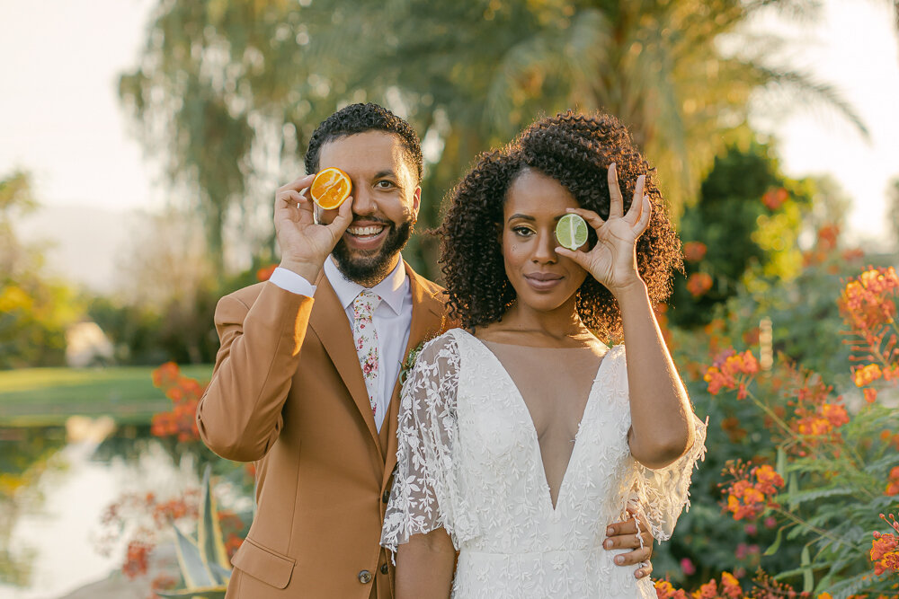 Couple holding fruit up to their face