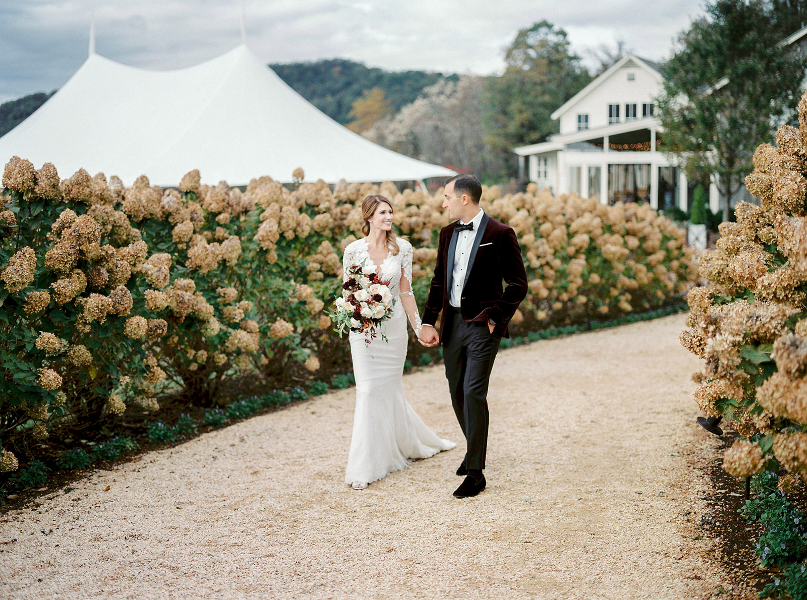 Couple walking down a lane of roses