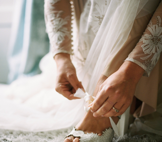 bride tying the strap on her shoe
