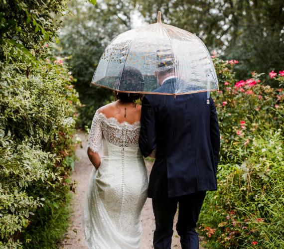 Couple holding an umbrella on a rainy wedding day