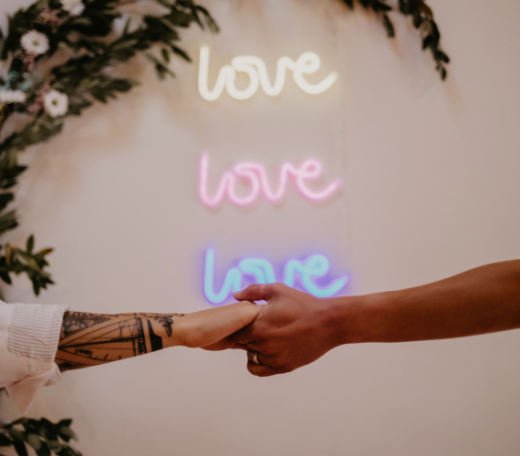 Couple holding hands with love neon sign in the back