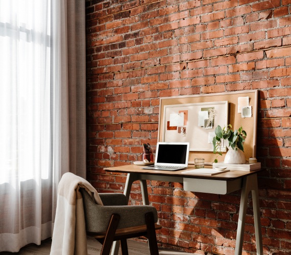 A desk with a chair and a brick wall behind it