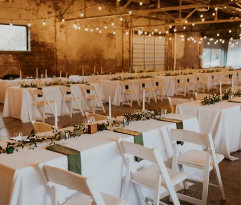 White long tables and white chairs set up for a wedding reception inside a barn