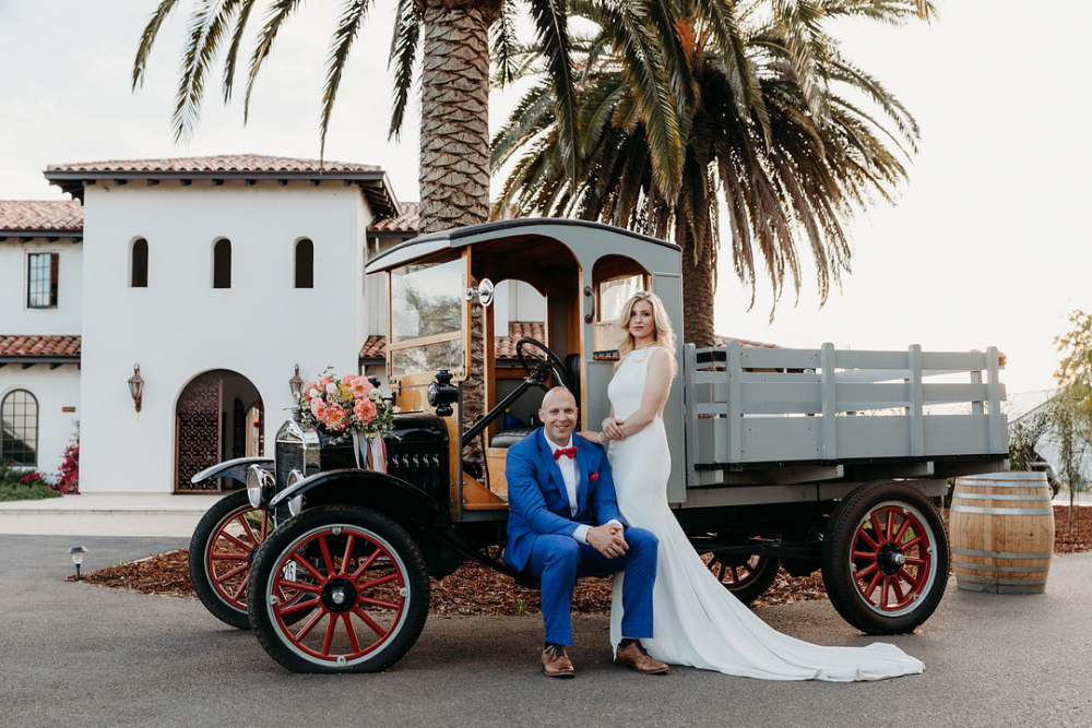 Newlyweds in Front of Vintage Car