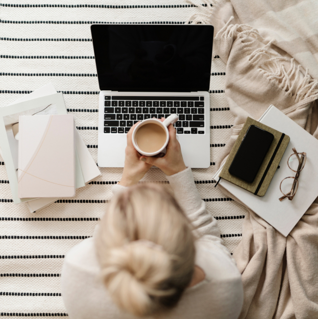woman with coffee and blond haired bun working on the floor with her computer