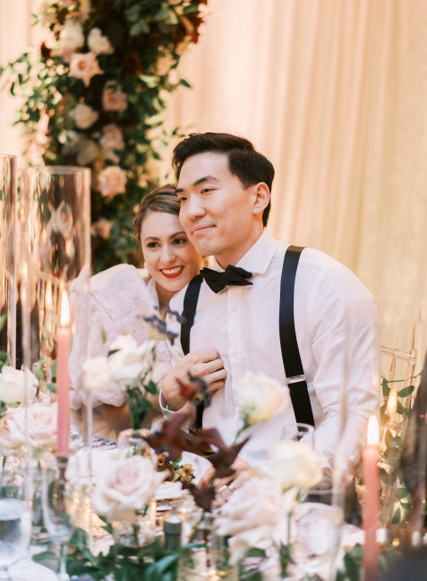 Newlyweds Smiling at Reception Table