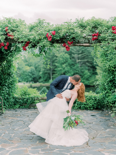 Newlyweds Kissing Under Green Arch