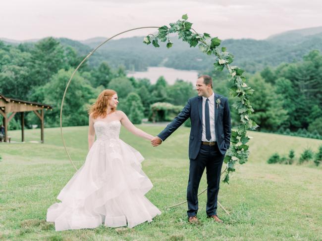 Newlyweds Standing Under Circular Arch
