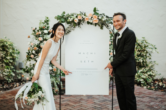 Newlyweds Pointing at Wedding Sign