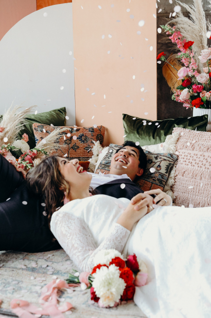 couple lying down together with confetti falling