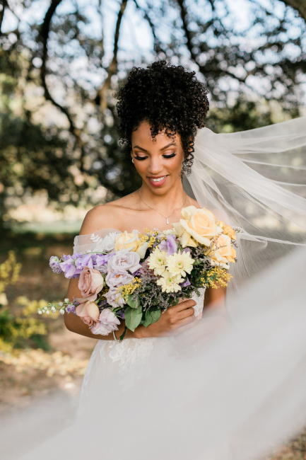 Bride holding purple and yellow bouquet