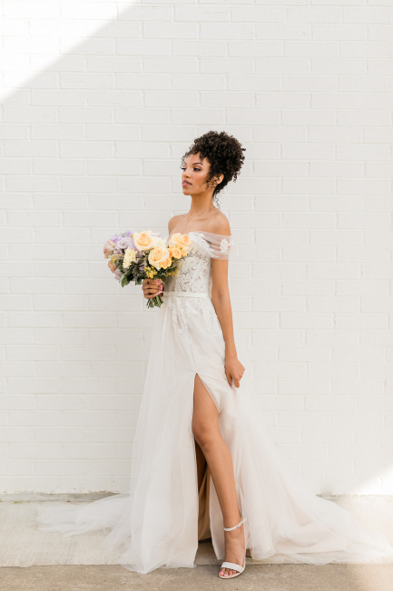 bride standing against white wall with yellow bouquet