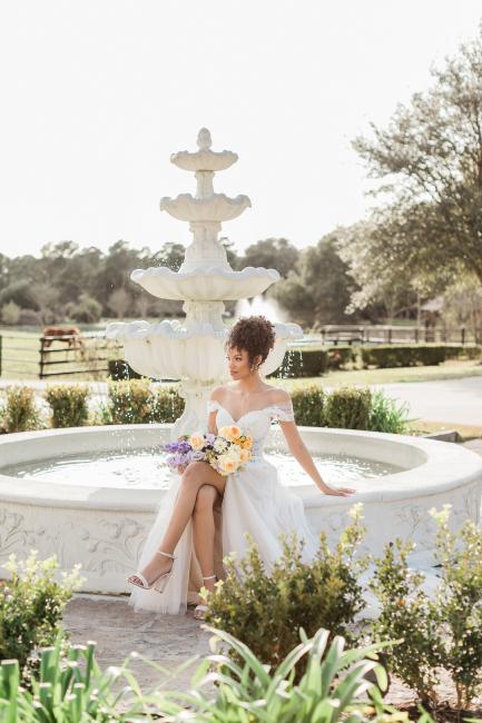 bride sitting on fountain