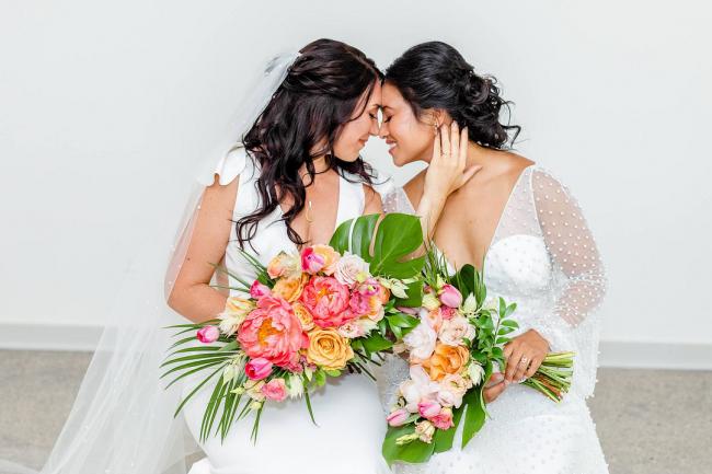 Brides holding tropical bouquets