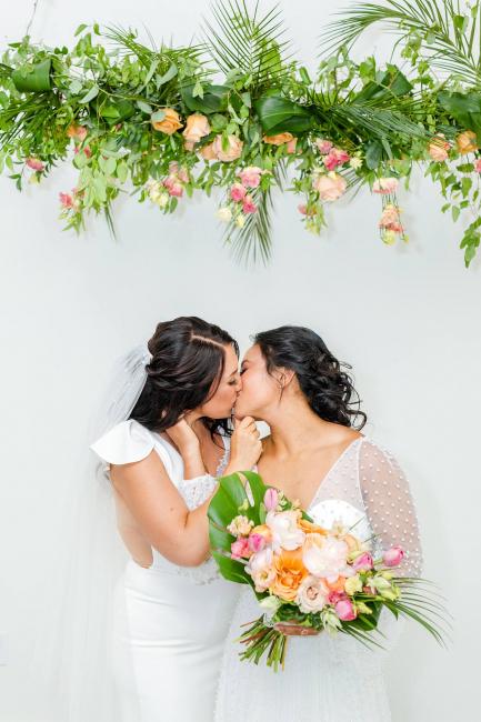 Brides kissing under tropical florals
