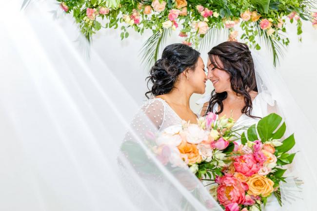 Brides kissing under veil