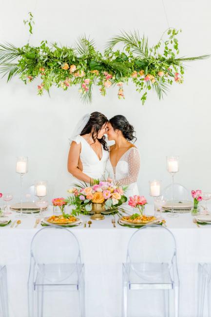 Brides kissing at reception table