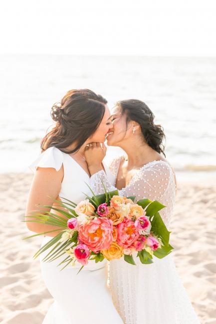 Brides kissing on beach