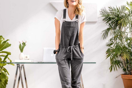 woman wearing grey overalls laughing in home office