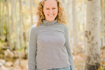 Krysta wearing a striped shirt and jeans standing in front of a forest backdrop