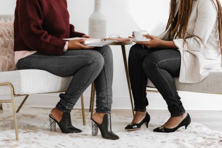 two women sitting wearing heels talking about business