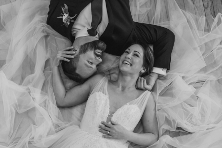 black and white photo of couple lying on a bed of tulle fabric