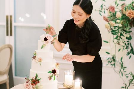 Ariel Chiu arranging florals on a white wedding cake
