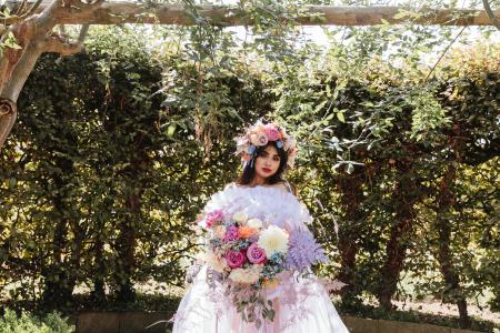 romantic maximalist bride holding bouquet beneath wooden arch