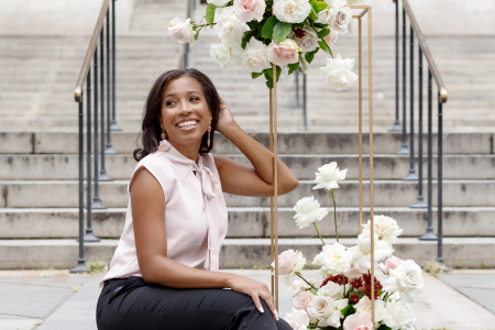 Simone Vega sitting on stairway with florals