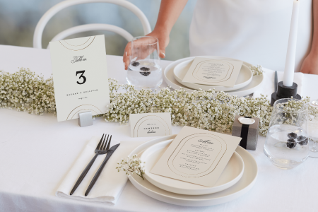 Person's hand setting a glass on a table laid with place settings and a floral runner