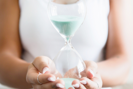 Person holding an hourglass sand clock